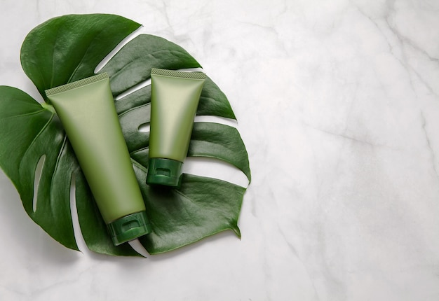 Green cosmetic tubes with leaf on marble background. flat lay, top view.
