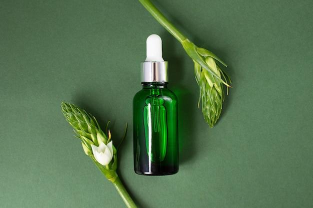 深緑色の背景に緑色の化粧品ボトル。周りに白い花が咲く葉、フレームのように見えます。コピースペースのある化粧品のモックアップ。