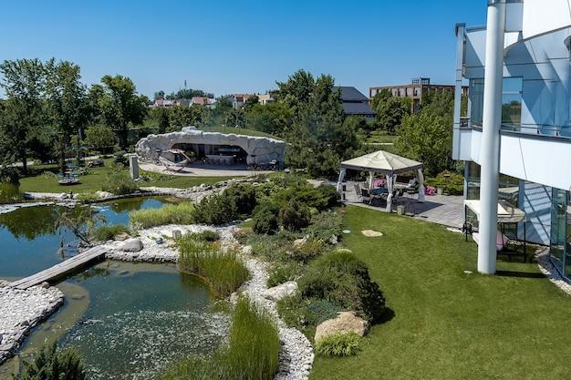 Зеленый двор загородного дома с искусственным прудом, патио и детской площадкой
