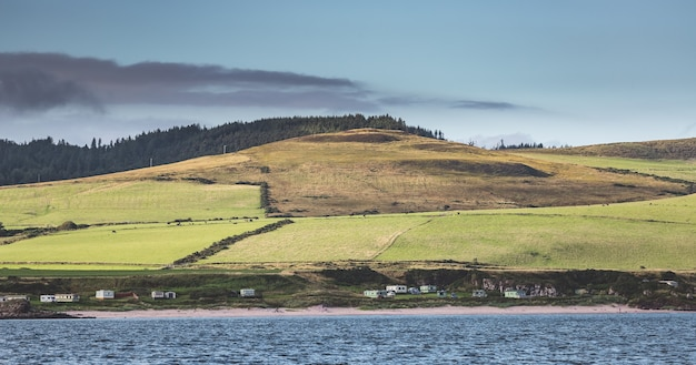 Green covered meadows settlement next to the northern ireland shoreline peacefulness countryside