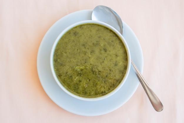 Зеленый крем-суп из шпината в белой миске, крупным планом