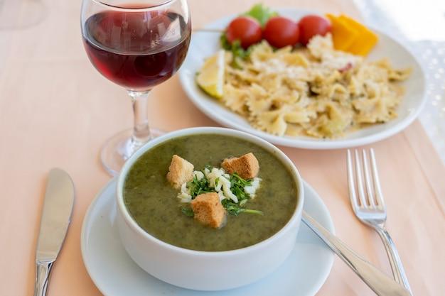 Зеленый крем-суп из шпината с гренками, сыром и свежей петрушкой в белой миске, крупным планом