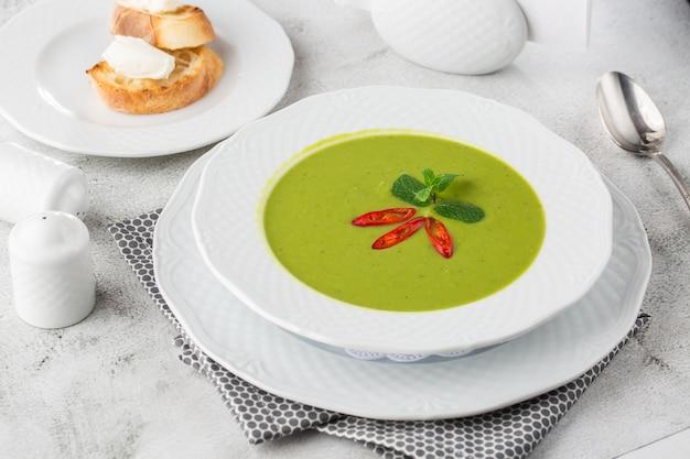 시금치와 브로콜리의 녹색 크림 스프. 치즈와 크루통이 추가되었습니다. 흰색 대리석 테이블. 개념 건강에 좋은 음식과 다이어트. 소박한 그릇에 시금치 수프의 신선한 수 제 크림.