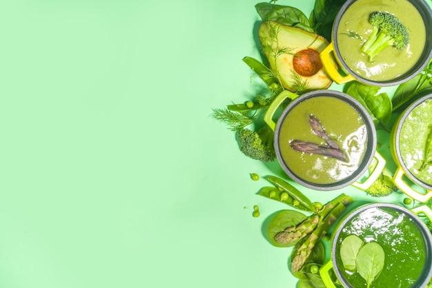 Набор зеленый крем-суп. разнообразие классических супов из зеленых овощей, в маленьких порционных горшочках - спаржа, шпинат, брокколи, зеленый горошек. на зеленом фоне копировать пространство вид сверху