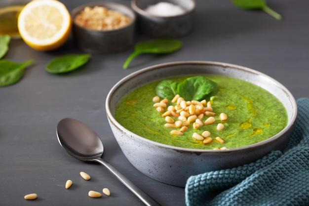 Green creamy cauliflower spinach soup on gray