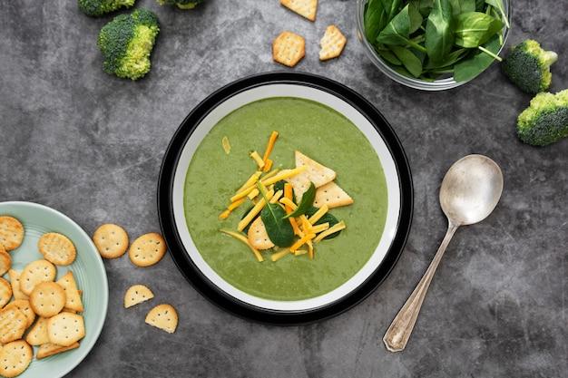 緑のクリーミーな野菜スープにクラッカーとチーズ。健康なほうれん草、ブロッコリーのベジタリアンデトックスフード。コピースペース。
