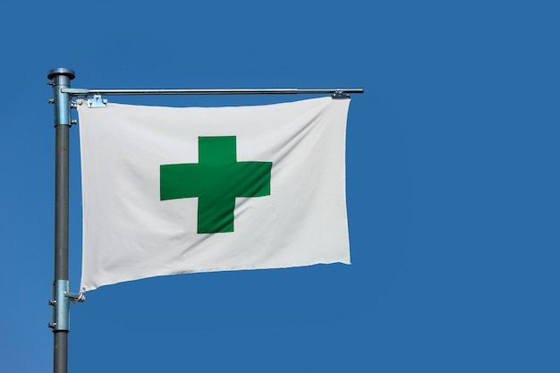 A green cross sign, safety first aid flag on blue sky background.