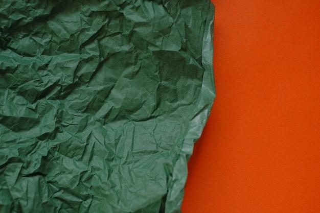 Зеленая мятой бумаги на оранжевом фоне.