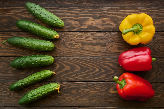 Green cucumbers and bell peppers on a wooden table