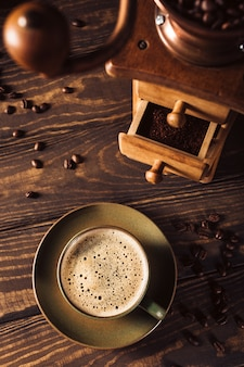 Green cup of coffee with coffee grinder