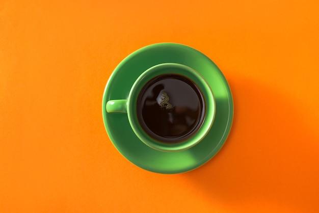 오렌지 배경에 녹색 컵 커피