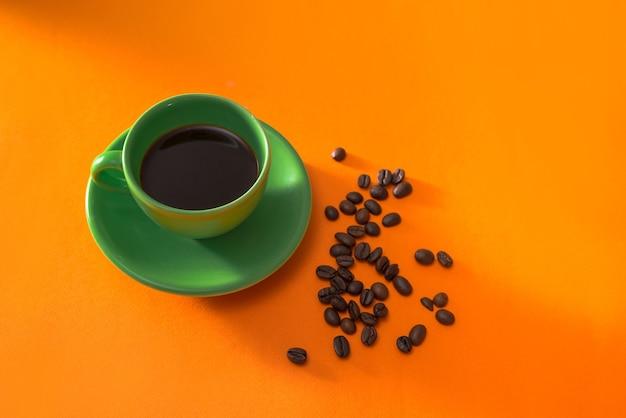 오렌지 바탕에 볶은 커피 원두와 커피의 녹색 컵