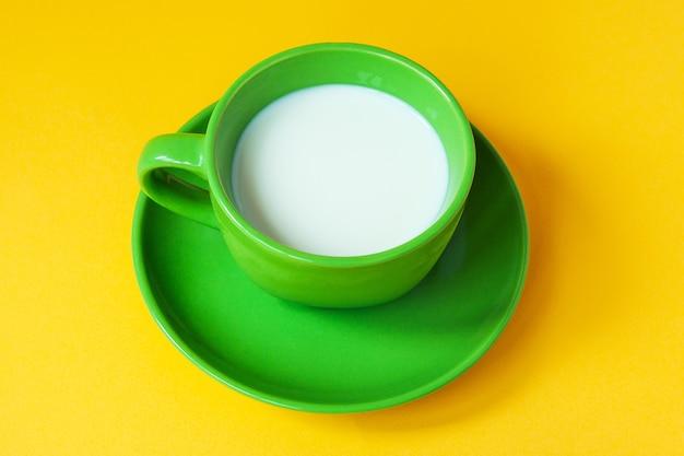 黄色のテーブルに新鮮な牛乳の緑のカップ
