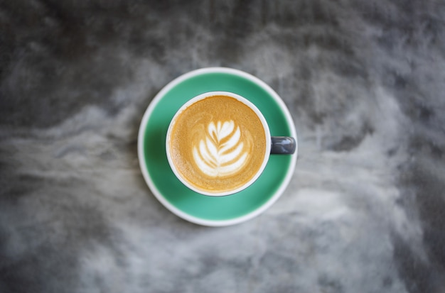 Green cup of tasty cappuccino.