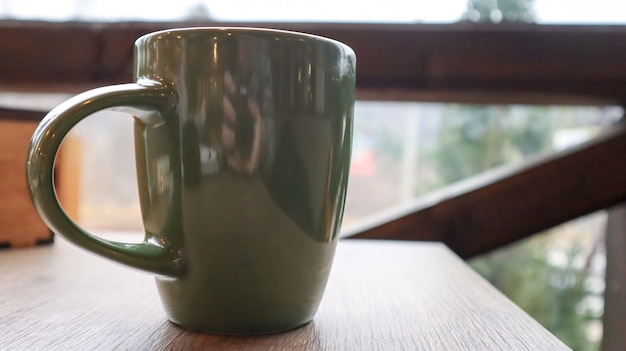 Green cup with tea or coffee on a wooden table on the balcony overlooking the street. hot drink on the table on the veranda of the summer cafe. soft focus.