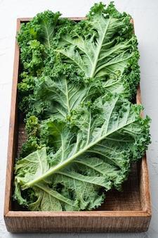 흰색 배경에 나무 상자에 녹색 곱슬 케일 식물 세트