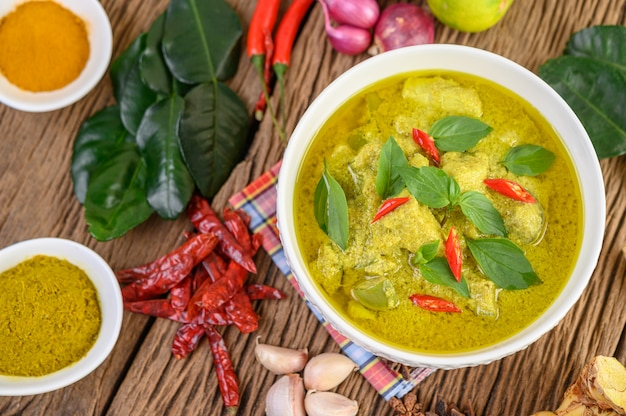 Green curry in a bowl and spices on wooden table.