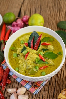 Green curry in a bowl with lime, red onion, lemon grass, garlic and kaffir lime leaves