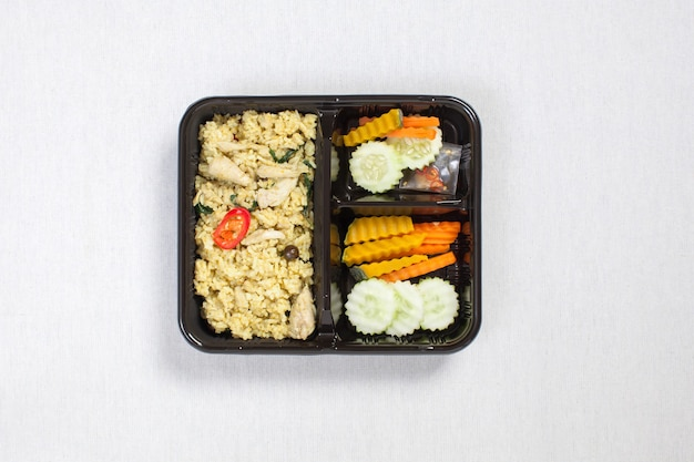 Green curry chicken rice put in black plastic box, put on a white tablecloth, food box, thai food.