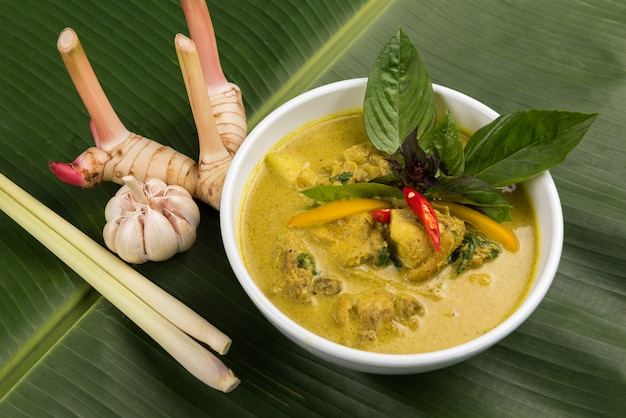 Green curry with chicken in bowl with galangal and lemon grass on banana leaf