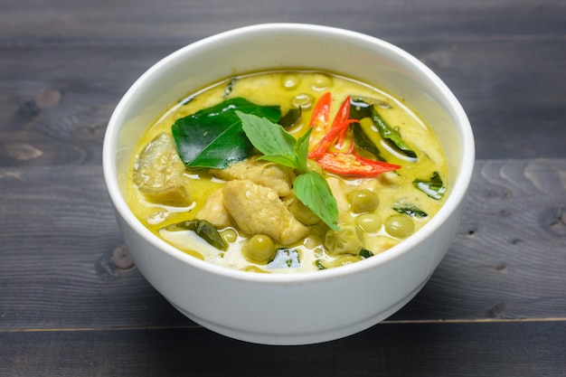 Green curry with chicken (kang keaw wan gai) on wooden background, thai local food