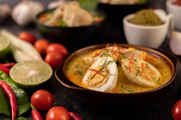 Green curry with eggs in black cups, with lemon, lemongrass, chili, and tomatoes.
