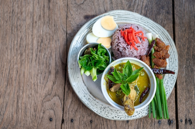 Green curry with rice vintage thai food on wooden table Premium Photo