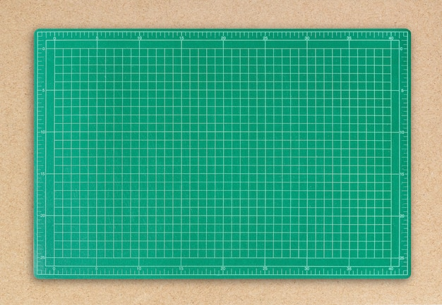 Green cutting mat on brown paper background.