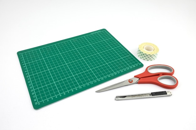 Green cutting mat with cutter scissors and tape roll of double-sided adhesive