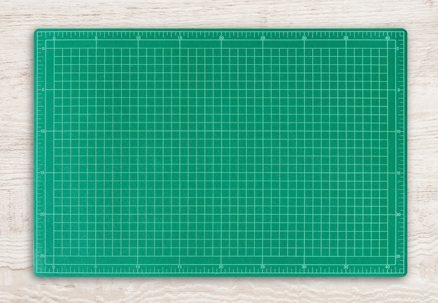 Green cutting mat on wood texture background.