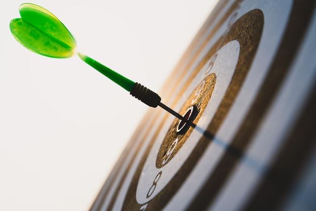 Зеленые стрелы дротиков в центре цели на фоне неба. бизнес-цель или успех цели и концепция победителя.