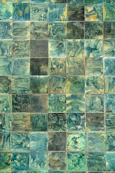 Green decorative tiles. the wall of the old house.