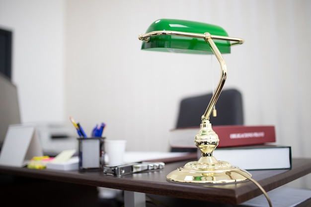 Green desktop lamp at an office with books and files