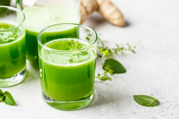 Green detox juice with ginger and mint in glasses and jars