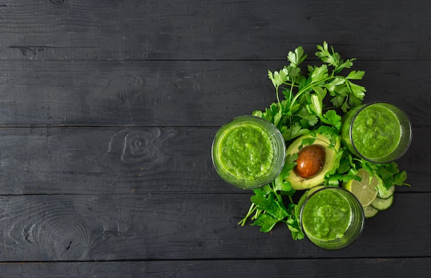 Green detox smoothie on a dark wooden background top view