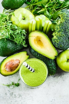 Green detox smoothie in a glass and ingredients for smoothie background, top view.