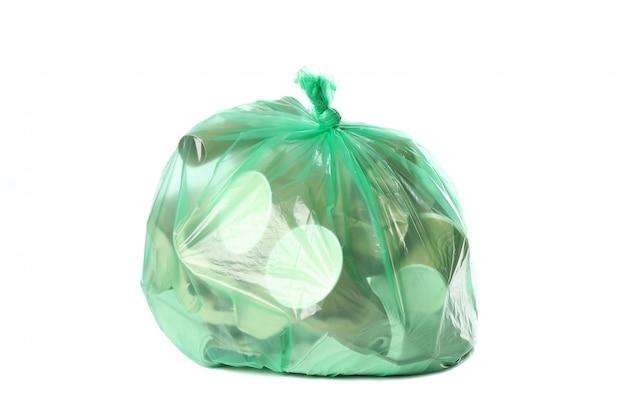Зеленая одноразовая сумка с разным мусором на белом фоне