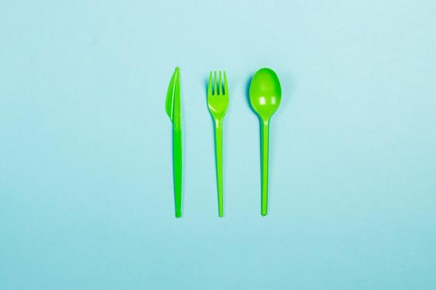 緑の使い捨てプラスチック食器と青色の背景に食品用電化製品。フォーク、スプーン、ナイフ。コンセプトプラスチック、有害、環境汚染、プラスチックを停止します。フラット横たわっていた、トップビュー。