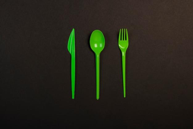 緑の使い捨てのプラスチック製食器および黒い背景に食品用電化製品。フォーク、スプーン、ナイフ。コンセプトプラスチック、有害、環境汚染、プラスチックを停止します。フラット横たわっていた、トップビュー。