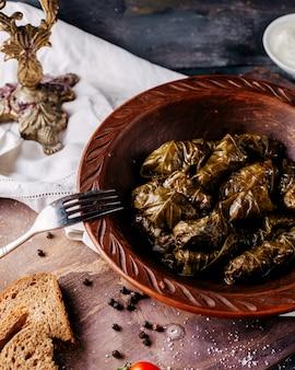 灰色の表面にある茶色の丸皿の中に充填された緑のドルマおいしい塩漬け肉