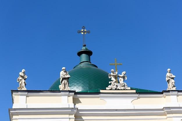 Зеленый купол с крестом и крышей со скульптурами на фоне голубого неба.