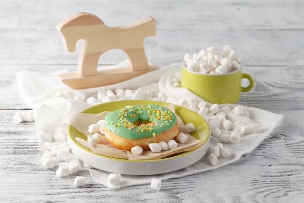 テーブルの上のミニマシュマロと緑のドーナツ