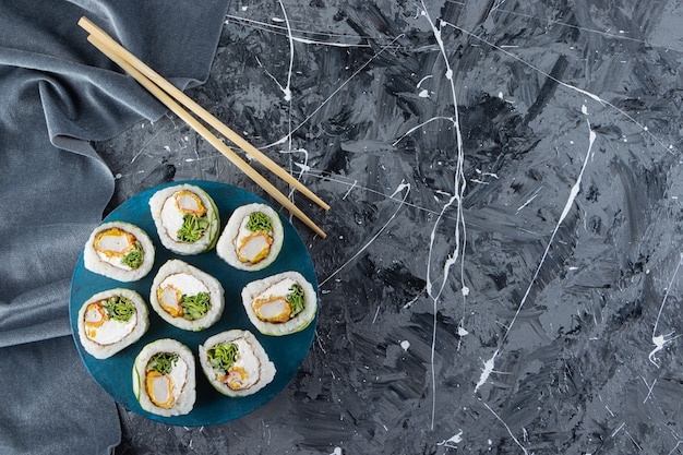 Green dragon sushi rolls and chopsticks on marble background.