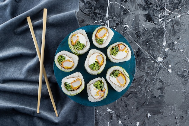 Green dragon sushi rolls placed on blue board.