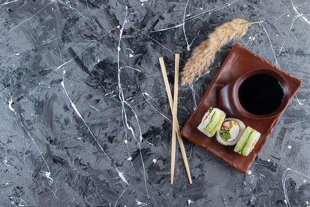 Суши-роллы с зеленым драконом на коричневой тарелке с соевым соусом.