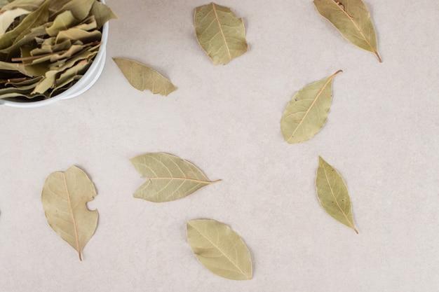세라믹 그릇에 녹색 말린 된 베이 잎.