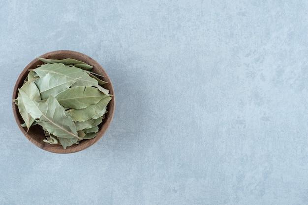 木製のカップに緑の乾燥した月桂樹の葉。高品質の写真