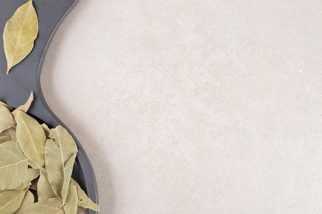 木製の大皿に緑の乾燥した月桂樹の葉。