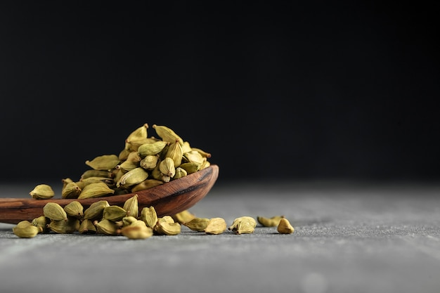 Зеленые сушеные семена кардамона в деревянной ложке на сером столе
