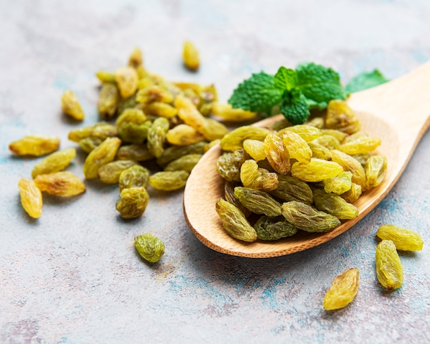 Green dried raisins on a grey concrete table Premium Photo
